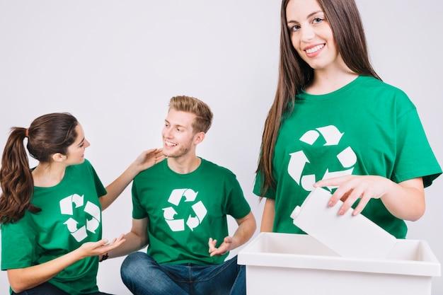 El retrato de una mujer sonriente que lanza la botella en recicla el cubo de basura