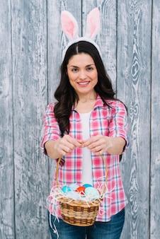 Retrato de la mujer sonriente que muestra la cesta de huevos de pascua contra fondo de madera