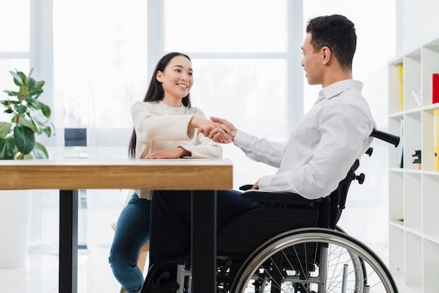Retrato de una mujer sonriente que sacude la mano con el hombre joven discapacitado que se sienta en la silla de rueda