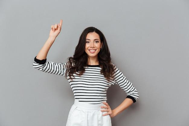 Retrato de una mujer sonriente que señala el dedo hacia arriba