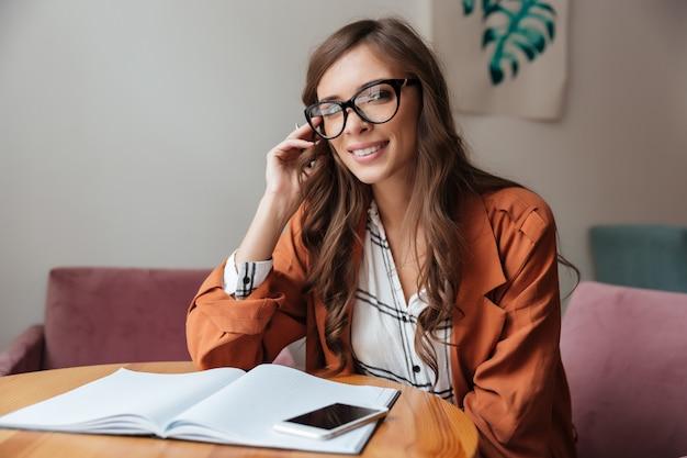 Retrato de una mujer sonriente sentada en la mesa