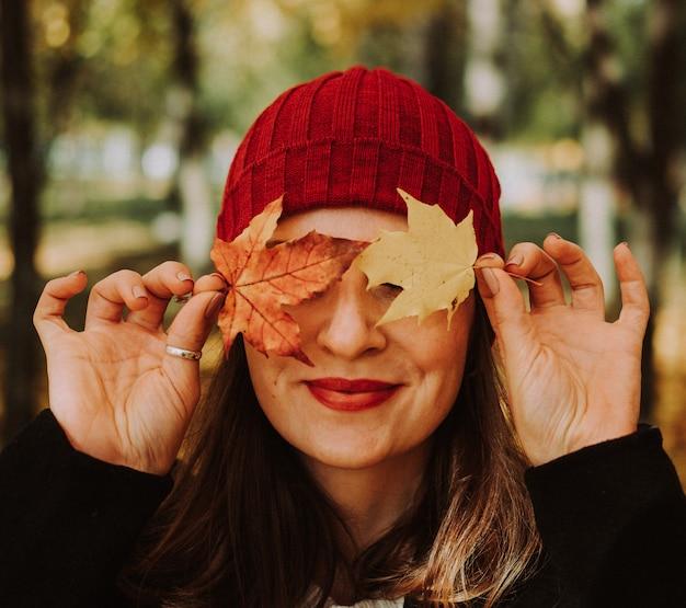 Retrato de mujer sonriente con sombrero rojo con hojas de naranja. temporada y vacaciones de otoño.
