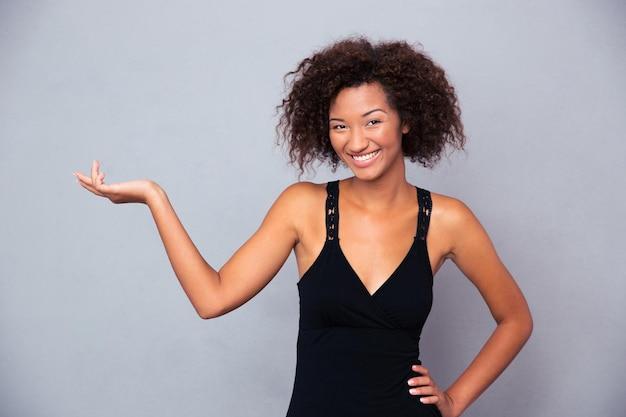 Retrato de una mujer sonriente sosteniendo copyspace en la palma sobre la pared gris y mirando al frente