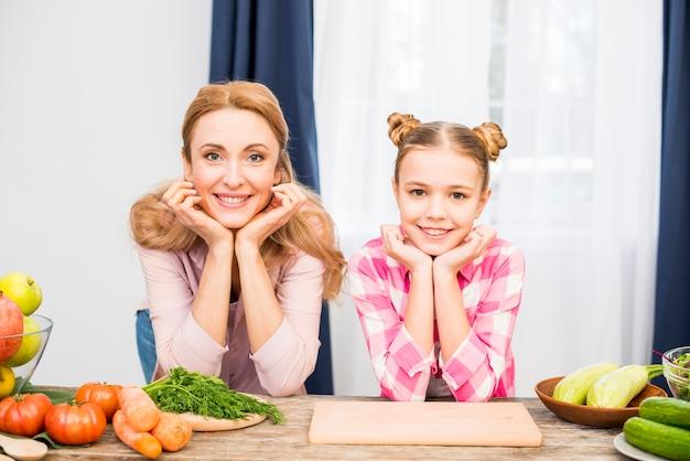 Retrato de una mujer sonriente y su madre que se inclinan sobre la mesa con la cabeza en la mano mirando a la cámara