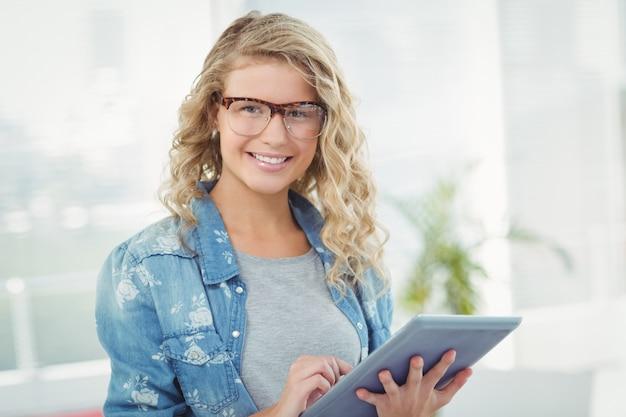 Retrato de mujer sonriente usando anteojos mientras usa la tableta digital