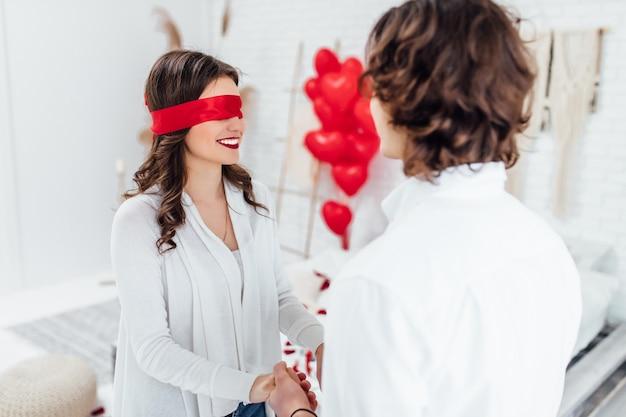 Retrato de mujer sonriente vistiendo rojo con los ojos vendados cogidos de la mano del novio en la habitación