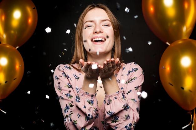 Retrato de mujer soplando confeti en la fiesta
