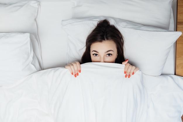 Retrato de mujer sorprendida acostada en la cama bajo edredón blanco y cubre su cuerpo