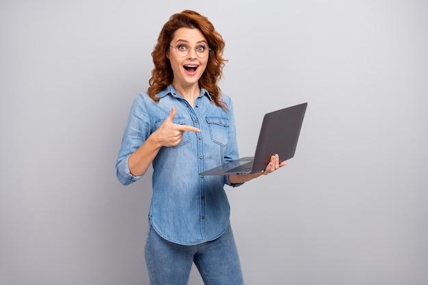 Retrato de mujer sorprendida y asombrada usar conexión inalámbrica de búsqueda de computadora portátil indica promoción de anuncios impresionado grito wow dios mío usar camisa de jeans de mezclilla aislada sobre pared de color gris