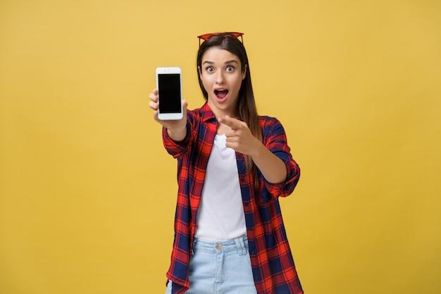 Retrato de una mujer sorprendida en tela casual mostrando un teléfono móvil con pantalla en blanco