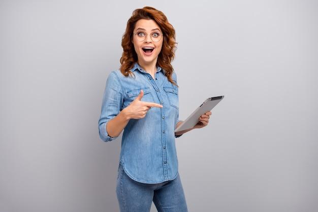 Retrato de mujer sorprendida uso tableta buscar noticias de redes sociales impresionado grito wow omg punto dedo índice desgaste estilo elegante camisa de mezclilla de moda aislada sobre pared de color gris