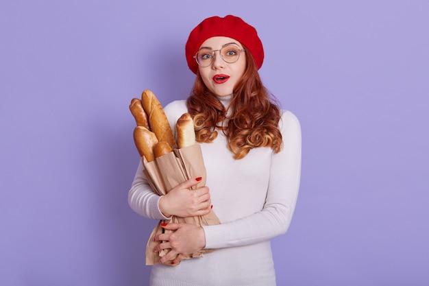 Retrato de mujer sorprendida viste boina y suéter casual blanco