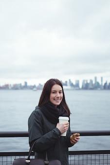 Retrato de mujer sosteniendo comida y bebida mientras está de pie junto a la baranda