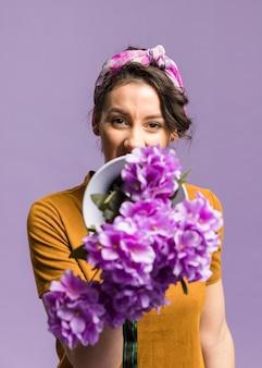 Retrato de mujer sosteniendo delante de su megáfono y flores