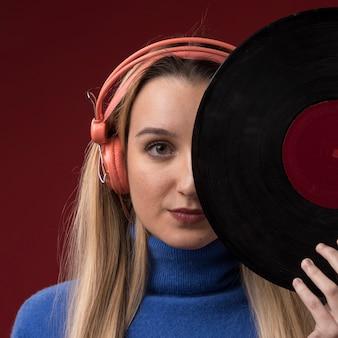 Retrato de una mujer sosteniendo un disco de vinilo