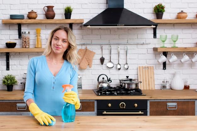 Retrato de una mujer sosteniendo una esponja y una botella de spray de detergente de pie en la cocina