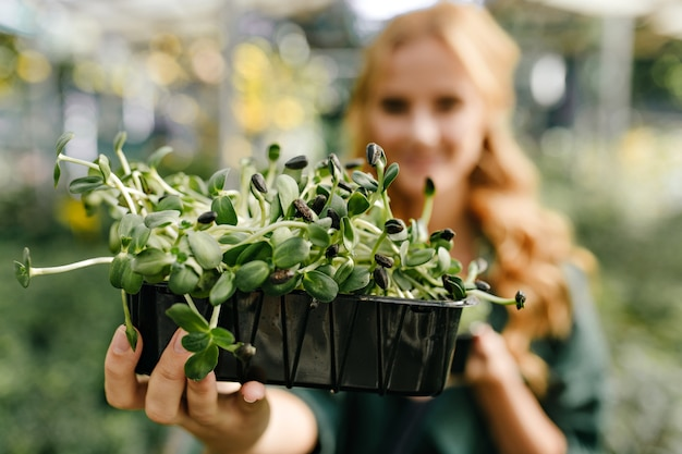 Retrato de mujer sosteniendo una hermosa planta perenne en maceta de plástico