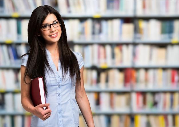 Retrato de una mujer sosteniendo un libro en una biblioteca