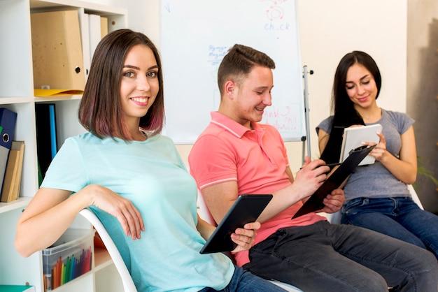 Retrato de una mujer sosteniendo una tableta digital sentada junto a sus amigas que estudian en la sala de estudio