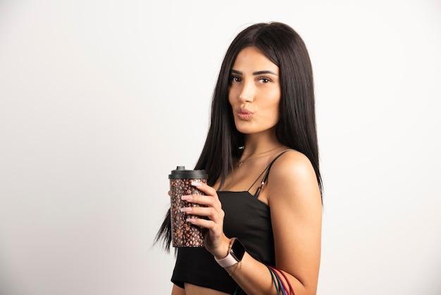 Retrato de mujer sosteniendo una taza de café sobre fondo beige. foto de alta calidad