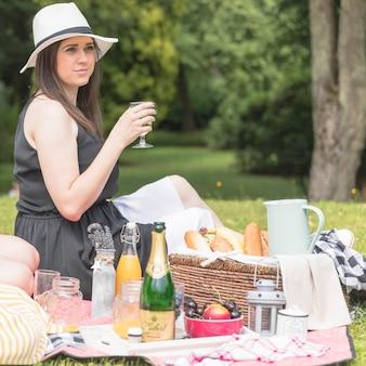 Retrato de mujer sosteniendo vidrio disfrutando de picnic