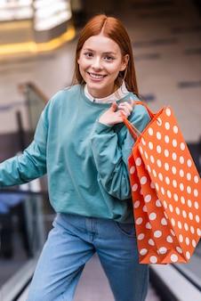 Retrato de mujer subir escaleras mecánicas y sosteniendo la bolsa de compras