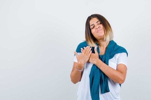 Retrato de mujer con suéter atado con las manos en el pecho en camiseta blanca y mirando encantada vista frontal