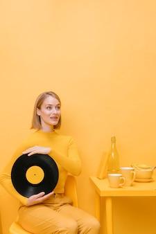Retrato de mujer sujetando un vinilo en un escenario amarillo