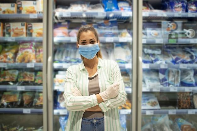 Retrato de mujer en supermercado con máscara de protección y guantes de pie junto a la comida en la tienda de comestibles