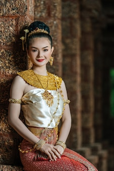 Retrato de mujer tailandesa encantadora en traje hermoso vestido tradicional, mujer con vestido típico tailandés sentado en sitio arqueológico o templo tailandés, cultura de identidad de tailandia