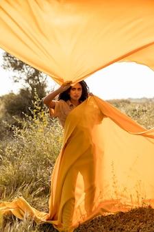 Retrato de mujer con tela en el campo