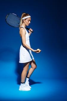 Retrato de mujer tenista con raqueta en hombro y bola en mano posando