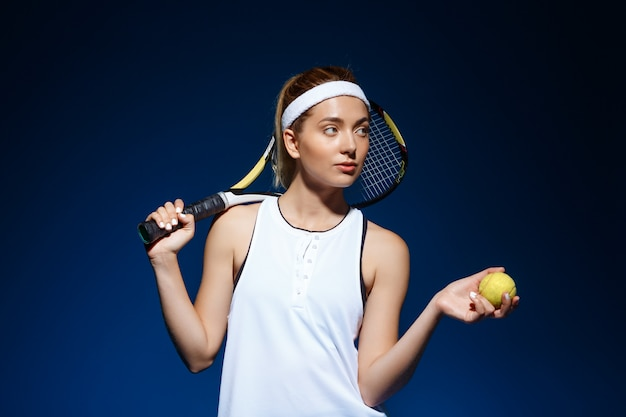 Retrato de mujer tenista con raqueta en hombro y pelota en mano posando