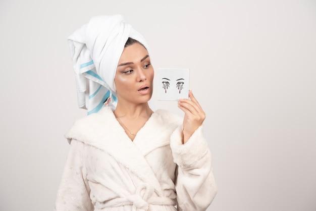 Retrato de mujer en toalla blanca mirando paleta de sombras de ojos
