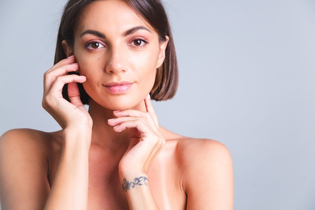 Retrato de mujer en topless con maquillaje y piel bronceada suave suave en la pared gris
