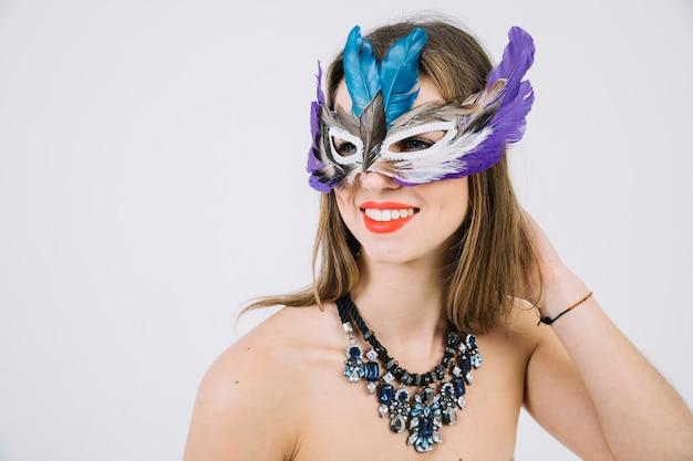 Retrato de una mujer en topless sonriente con máscara de plumas