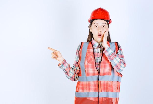 Retrato de mujer trabajador de la construcción apuntando sobre fondo blanco.