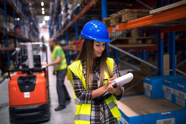 Retrato de mujer trabajadora de almacén comprobando el inventario en el departamento de almacenamiento mientras su compañero de trabajo operando la carretilla elevadora en segundo plano.