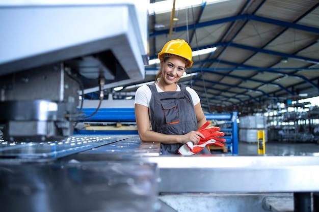 Retrato de mujer trabajadora de fábrica en uniforme protector y casco permanente por máquina industrial en la línea de producción