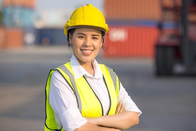 Retrato de mujer trabajadora ingeniero logístico capataz en casco y seguridad en contenedores de carga