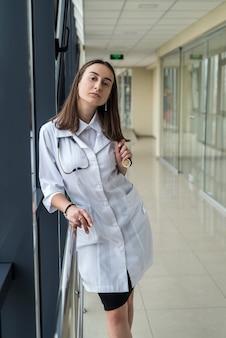 Retrato de mujer trabajadora de la salud pasante de pie en el pasillo del hospital moderno. concepto medico