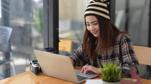 Retrato de mujer trabajando con ordenador portátil y papelería sobre mesa de madera en la cafetería.