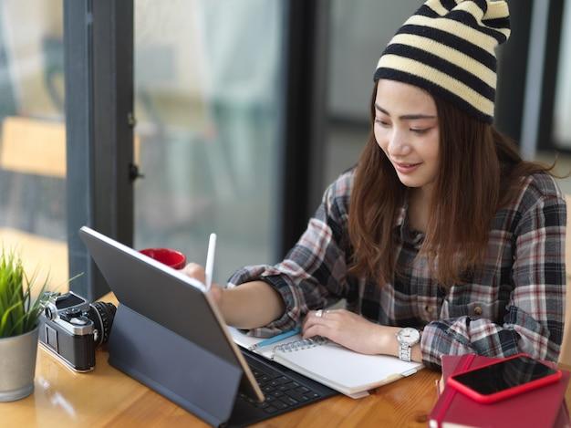 Retrato de mujer trabajando con tableta y papelería sobre mesa de madera en la cafetería.
