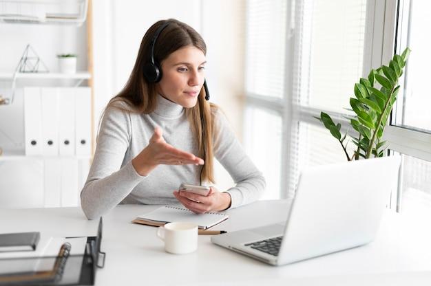 Retrato de mujer en el trabajo con videollamada