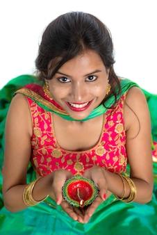 Retrato de una mujer tradicional india sosteniendo diya, mujer celebrando diwali o deepavali con la celebración de la lámpara de aceite durante el festival de la luz en blanco