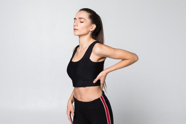 Retrato de una mujer en un traje de fitness experimentando dolor de cuello, hombro y espalda aislado en la pared blanca