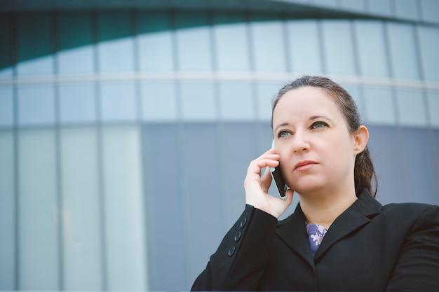Retrato de una mujer en un traje hablando por un teléfono serio