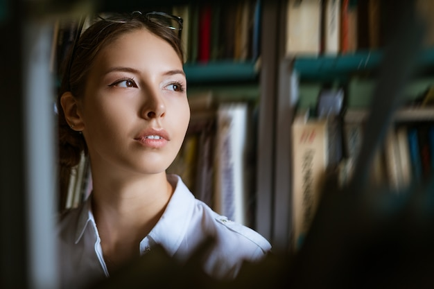 Retrato de mujer con el trasfondo de libros en la biblioteca, mirando a través de los estantes de libros. el concepto de preparación para los exámenes.
