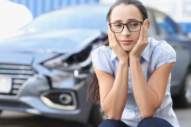 Retrato de una mujer triste en el fondo del concepto de accidente y consecuencias de coche roto