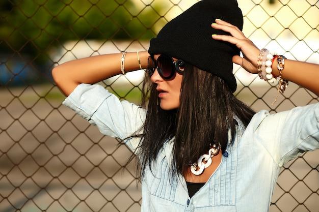 Retrato de mujer urbana moderna joven elegante modelo de chica en jeans casuales pantalones cortos de tela al aire libre en la calle con gorra negra